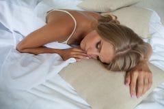 Den blonda flickan sover i en säng i sovrummet, drömmer Arkivfoto