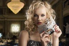 Den blonda flickan tar en silvermaskering med båda händer Arkivbild