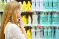 Den blonda flickan väljer abstergent shoppar in Arkivfoto