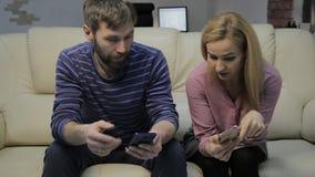Den blonda frun och maken som sitter på soffan, använder smartphones och betalar inte uppmärksamhet till varandra arkivfilmer