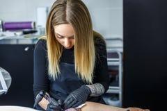Den blonda konstnären drar en tatuering med maximal koncentration Arkivfoto