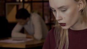 Den blonda kvinnan arbetar på hennes projekt i kafét stock video