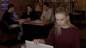 Den blonda kvinnan avslutar sig för att arbeta på hennes dator i modernt kafé arkivfilmer