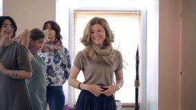 Den blonda kvinnan binder halsduken på stilkurs inom studio lager videofilmer