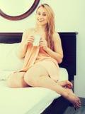 den blonda kvinnan dricker te i morgonen efter en dusch Fotografering för Bildbyråer