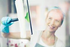 Den blonda kvinnan gör ren fönstret royaltyfri bild