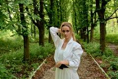 Den blonda kvinnan g?r l?ngs den kastanjebruna gr?nden i staden parkerar bara r royaltyfria foton