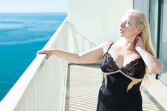 Den blonda kvinnan i en svart korsetterar på balkongen som förbiser havet royaltyfri fotografi