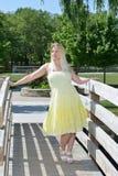 Den blonda kvinnan i gula sundress poserar på bron Arkivbild