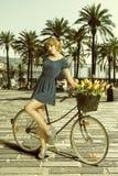 Den blonda kvinnan i sexigt poserar nära cykeln Royaltyfri Fotografi