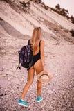 Den blonda kvinnan i swimwearbikini promenerar stranden med solnedgångfärger Flicka på semester Arkivfoton