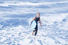 Den blonda kvinnan i wetsuit och simning stiger ombord i vattnet Arkivfoto