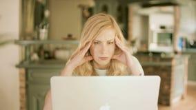 Den blonda kvinnan koncentrerade mycket på hennes bärbar dator stock video