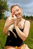 Den blonda kvinnan kramar en vit höna royaltyfri fotografi