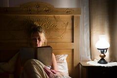 Den blonda kvinnan ligger i gammal säng och läser boken Royaltyfria Foton