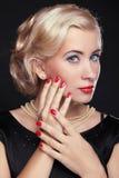 Den blonda kvinnan med det manicured sminket och rött spikar över svart, stu Arkivfoto