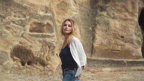 Den blonda kvinnan med en nätt framsida går av en forntida stad som snidas in i, vaggar nära fladdrande h?rwind _ arkivfilmer