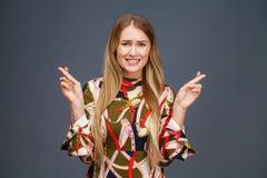 Den blonda kvinnan med fingrar korsade Begrepp av att önska eller att be fotografering för bildbyråer