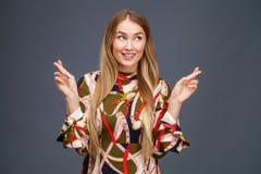 Den blonda kvinnan med fingrar korsade Begrepp av att önska eller att be arkivfoton