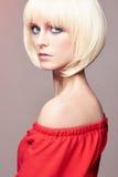 Den blonda kvinnan med guppar frisyren, sminket, röd klänning arkivbilder