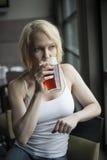 Den blonda kvinnan med härliga blått synar dricka exponeringsglas av ljust öl Royaltyfri Bild