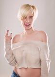 Den blonda kvinnan med kort hår och ett härligt leende med det isolerade pekfingret Royaltyfri Bild