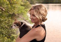 Den blonda kvinnan rymmer hennes chihuahuahund Royaltyfri Fotografi