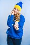 Den blonda kvinnan ser telefonen Arkivfoton