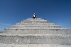 Den blonda kvinnan sitter ?verst av den konkreta trappaplattformen mot en bl? himmel Negativ utrymmesammans?ttning, med massor av royaltyfri bild