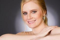 Den blonda kvinnan som ler stora Head skuldror, poserar Arkivfoto