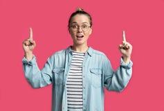 Den blonda kvinnan som pekar fingrar kopierar upp till, utrymme som isoleras över rosa bakgrund royaltyfri foto