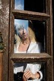 Den blonda kvinnan st?r i den gamla tr?d?rr?ppningen gammalt tr? f?r d?rr r arkivbilder