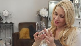 Den blonda kvinnan väljer ett exponeringsglas för vin royaltyfri bild