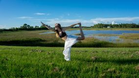 den blonda kvinnanegro spiritual som gör anseendet för yogakonungdansen som drar pilbågen Natarajasana/Dandayamana Dhanurasana, p royaltyfri fotografi