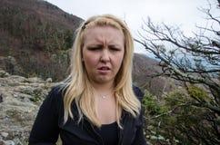 Den blonda kvinnliga fotvandraren ser sjuk och äcklad, når han har avslutat en naturvandring Ögon skelas royaltyfri fotografi
