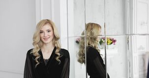 Den blonda kvinnliga modellen med lockigt hår i svart negligé ler nära spegeln lager videofilmer