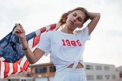 Den blonda kvinnliga modellen rymmer upp amerikanska flaggan Arkivbild