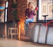 Den blonda kvinnlign dricker varmt kaffe nära fönstret Royaltyfri Foto