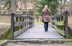 Den blonda kvinnlign går över träbron royaltyfri foto