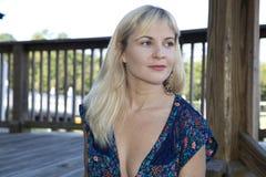 Den blonda kvinnlign som bär en baddräkt, täcker upp att se i väg från kamera Royaltyfri Foto