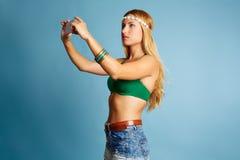 Den blonda långa hårflickan med jeans kortsluter selfiefotoet Royaltyfria Bilder