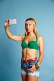 Den blonda långa hårflickan med jeans kortsluter selfiefotoet Arkivbild