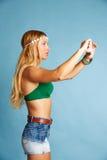 Den blonda långa hårflickan med jeans kortsluter selfiefotoet Arkivfoton
