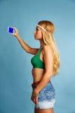 Den blonda långa hårflickan med jeans kortsluter selfiefotoet Arkivbilder