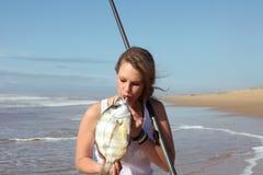 Den blonda ladyen kysser en fisk som hon fångade Royaltyfri Foto