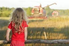 Den blonda lantgårdflickan i röda prickungar panorerar att se fältet med att skörda skördetröskan royaltyfri fotografi
