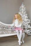 Den blonda lilla flickan sitter på en soffa och trycker på en gåvaask i jul Fotografering för Bildbyråer