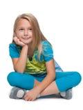 Den blonda lilla flickan sitter på golvet Royaltyfri Foto