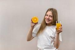 Den blonda lyckliga flickan rymmer i hennes hand ett exponeringsglas av ny fruktsaft banta sunt Veggie och strikt vegetarian royaltyfri bild
