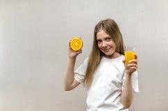 Den blonda lyckliga flickan rymmer i hennes hand ett exponeringsglas av ny fruktsaft banta sunt Veggie och strikt vegetarian royaltyfria bilder